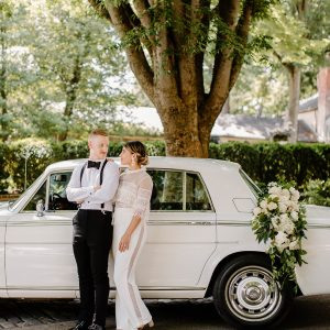 Classic white car with a couple in front of it on their wedding day and flower garland on the trunk
