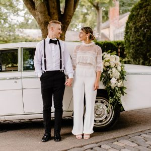 A couple on their wedding day holding hands in front of a white, classic car