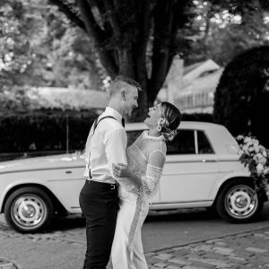Black and white photo of a couple laughing and embracing on their wedding day in front of a classic white car