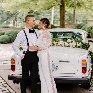 A couple standing in front of a white, classic car with a floral garland on the trunk