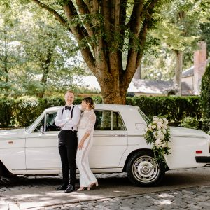 Wide shot of a couple on their wedding day standing in front of a white, classic car with a flower garland on the trunk