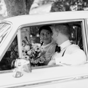 Black and white image of a couple on their wedding day driving away in a classic car and smiling at each other