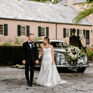 A couple on their wedding day holding hands in front of a silver, classic car with a floral wreath attached to the grill