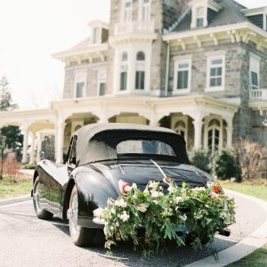 A black classic car decorated with flowers on its bumper