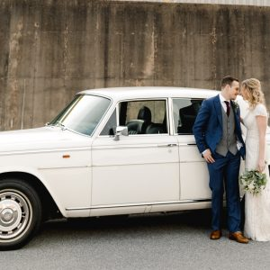 A bride and groom on their wedding day kissing in front of a white classic car