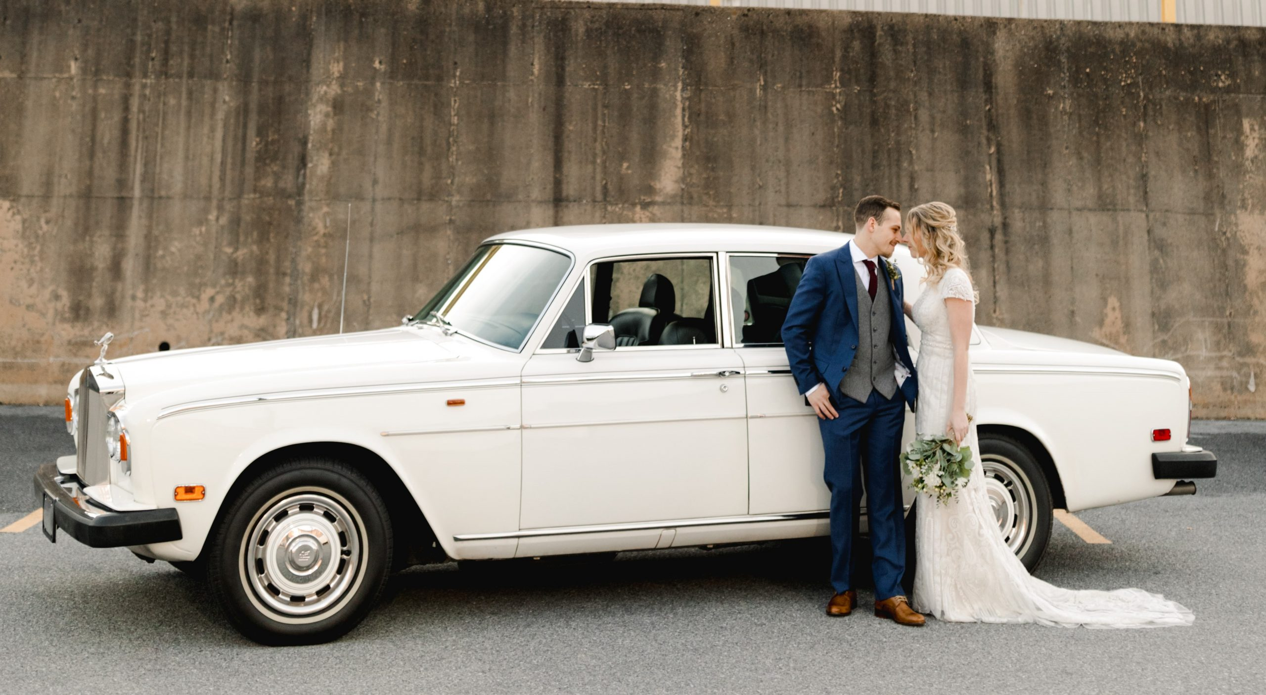 A bride and groom standing in front of a white classic car