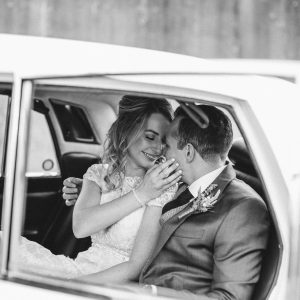 A couple kissing inside of a white classic car on their wedding day