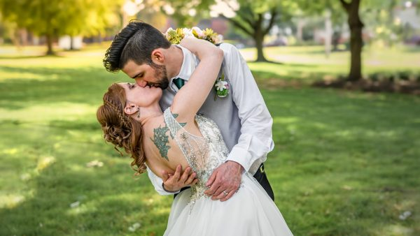 A groom dip kissing his bride on their wedding day