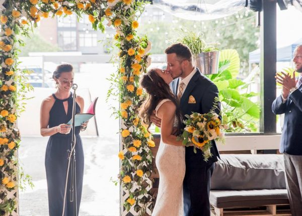 A couple kissing underneath a wedding arch that's decorated with sunflowers