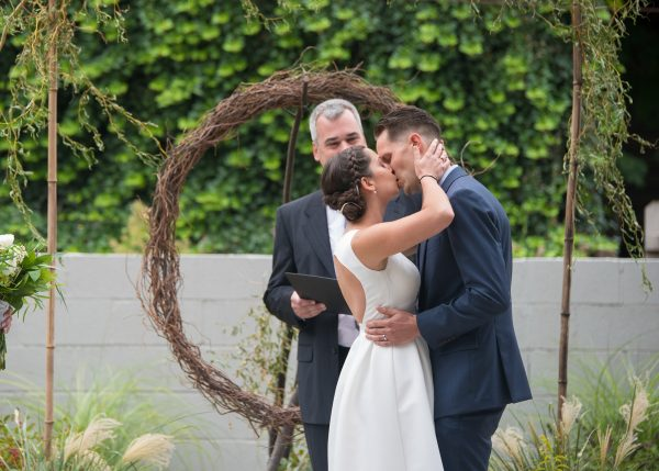 Bride and groom kissing at their wedding ceremony with a circular arbor in the background