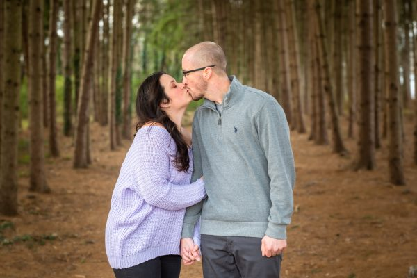 An engaged couple kissing while they go for a walk in the woods