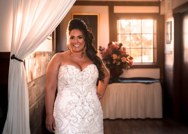 A bride, smiling on her wedding day and wearing a sparkly wedding gown