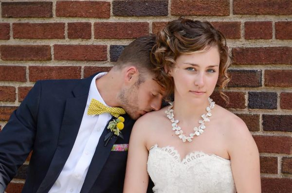 A groom, kissing his bride on the shoulder