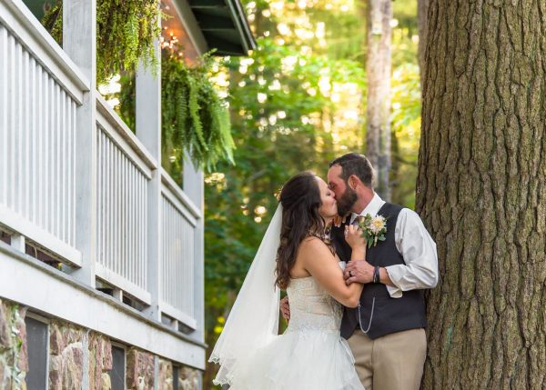 Bride and groom on their wedding day kissing against a tree