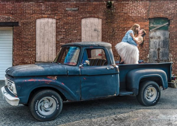 A groom dip kissing his bride on their wedding day while standing in the bed of a vintage pickup truck